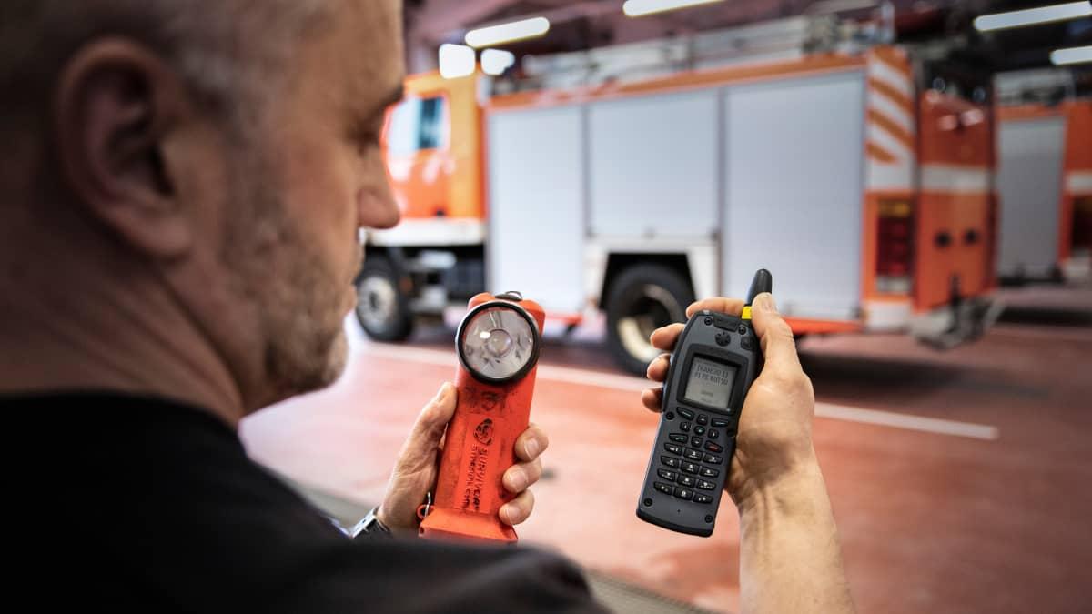 Pirkanmaan pelastuslaitoksen paloesimies Jari Leppänen kädessään taskulamppu ja Virve-puhelin Kangasalan paloasemalla.