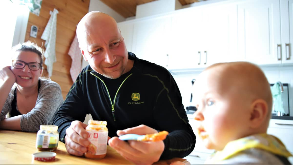 Juho Vesalainen syöttää iloisena poikaansa Otsoa. Äiti Virpi Lappi katsoo vieressä hymyillen.