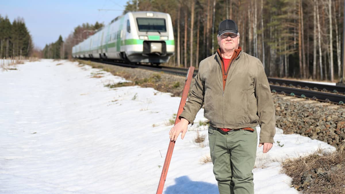 Ossi Hämäläinen seisoo raiteen varrella, kun juna menee selän takaa ohi