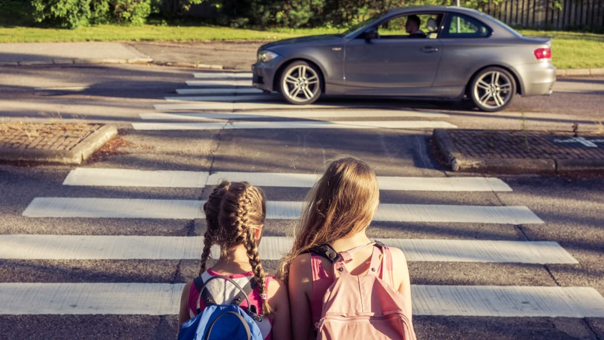 Kaksi lasta ylittämässä suojatietä. Taustalla ajaa auto.