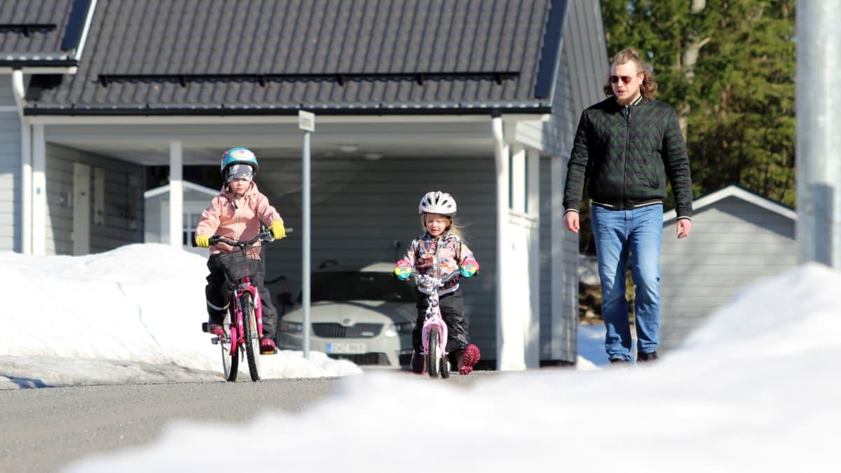 Jaakko Palmunen kävelee kadulla ja vahtii lapsiaan, jotka pyöräilevät.