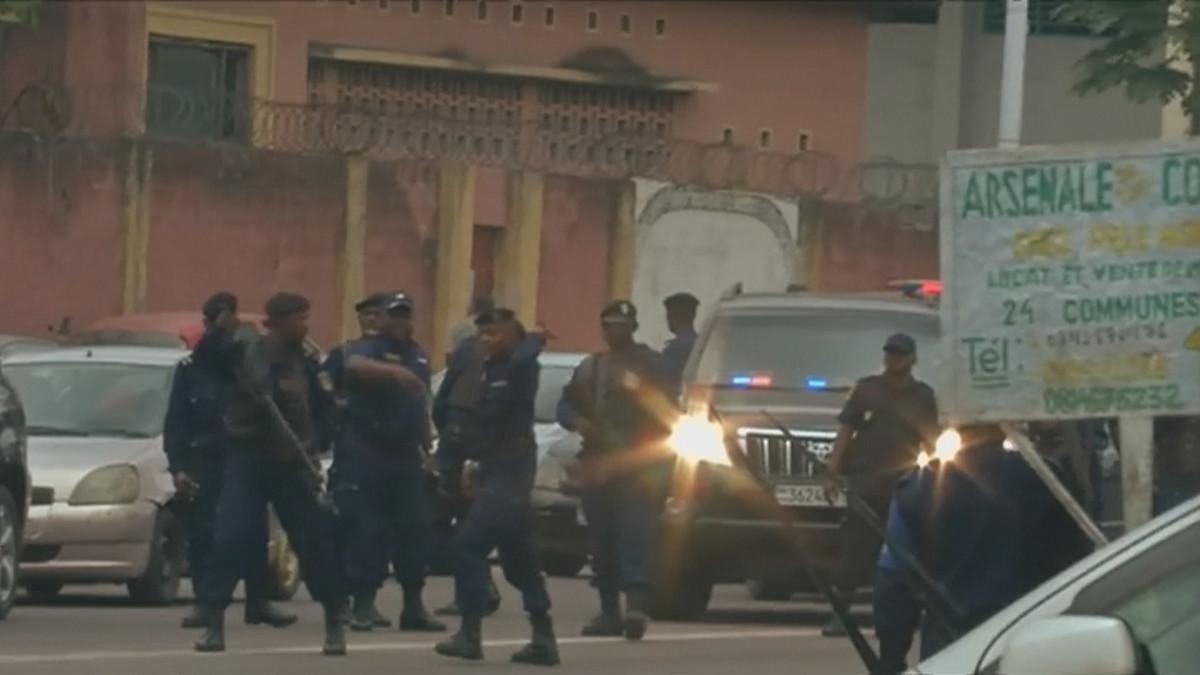 Joukko poliiseja tummissa univormuissa parveilee kadulla autojen keskellä aseita käsissään.