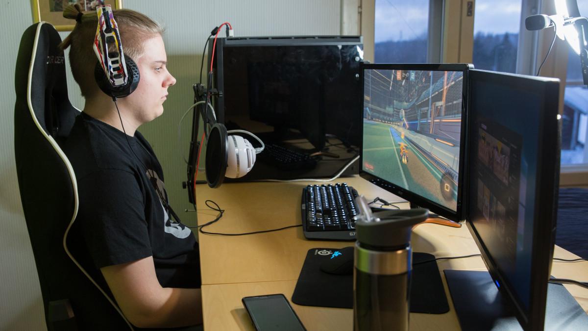 Nuori mies pelaamassa tietokoneella.