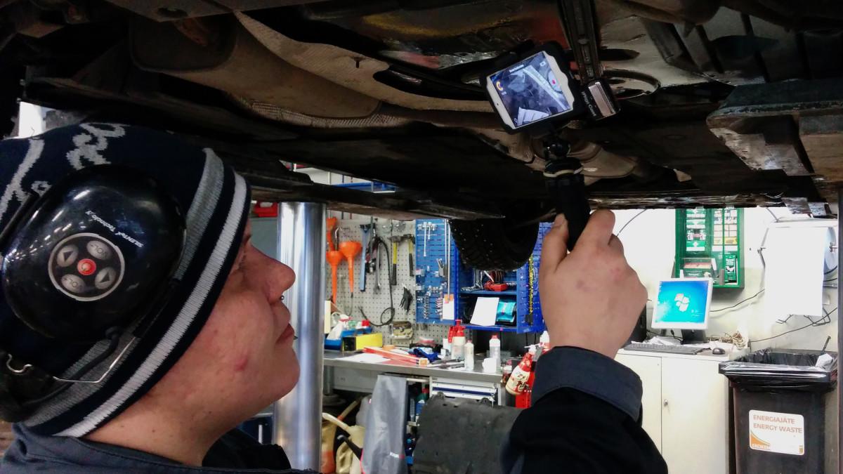 Autoasentaja kuvaamassa videota auton alla