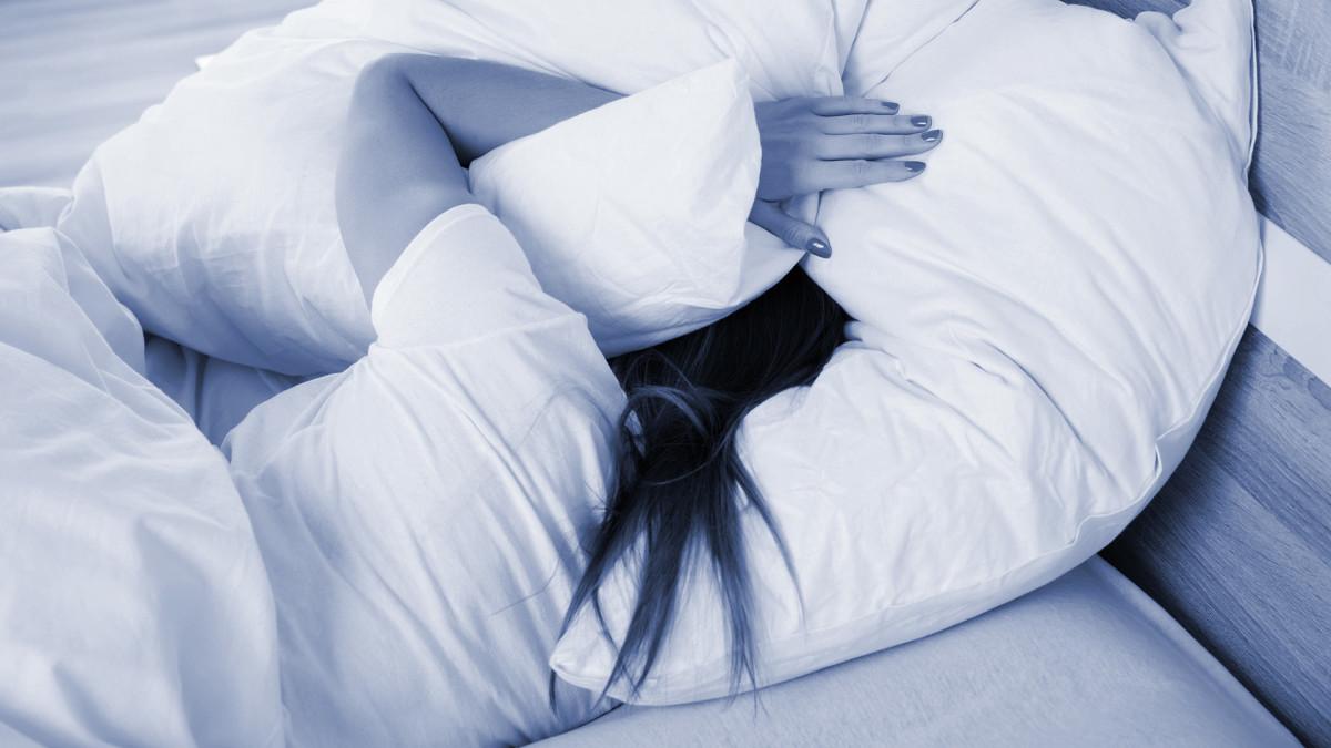 nainen sängyssä, tyynyt korvilla