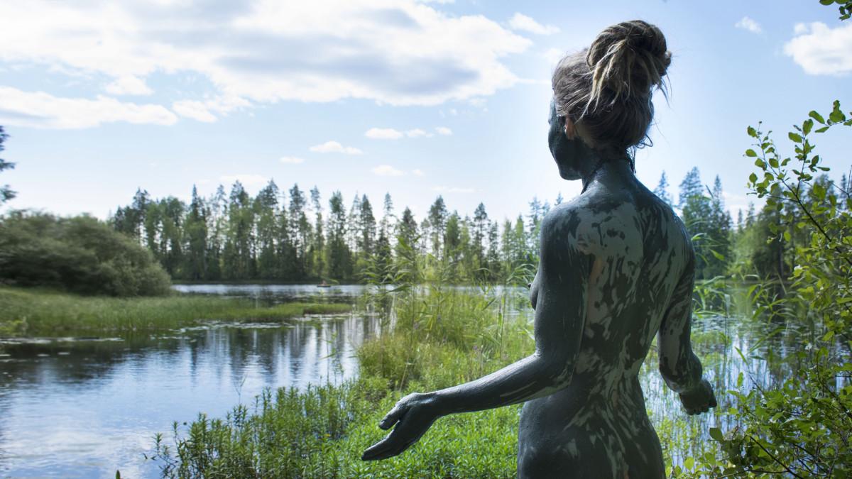Nainen savikylvyssä keskisuomalaisen järven rannalla.