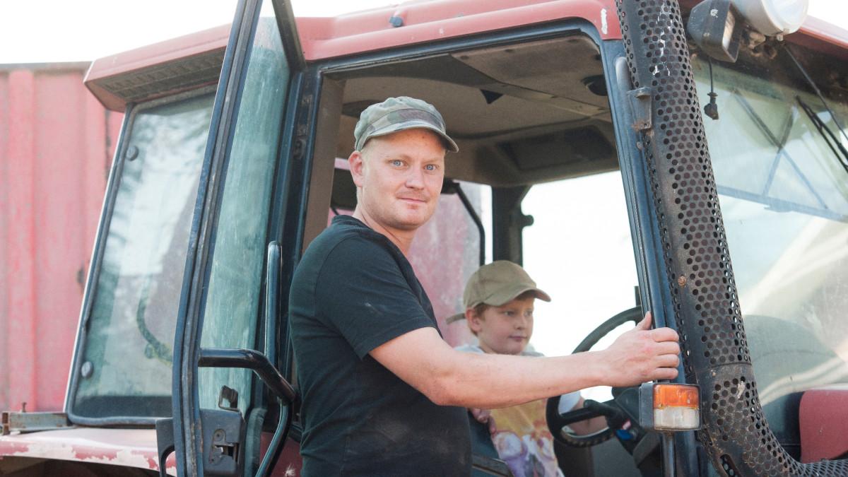 Isä ja poika traktorin ääressä.