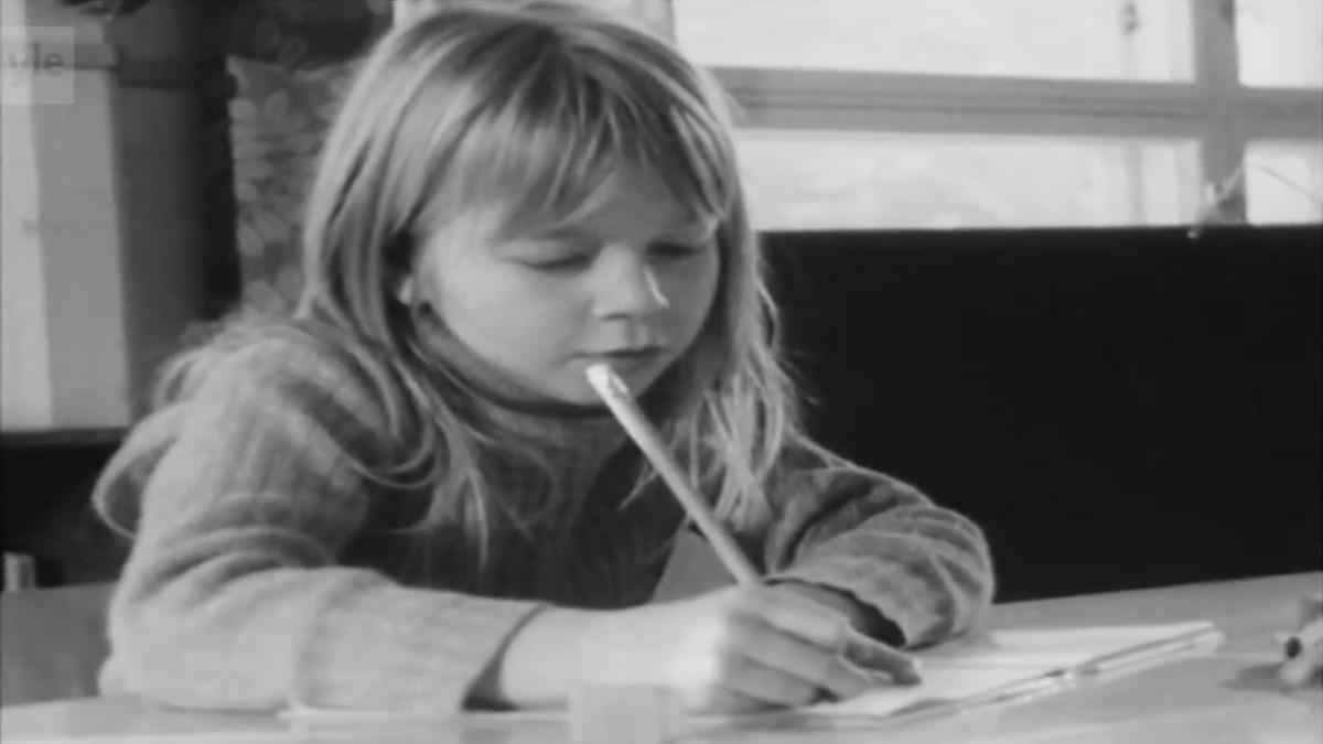 Tyttö kirjoittaa vihkoon.