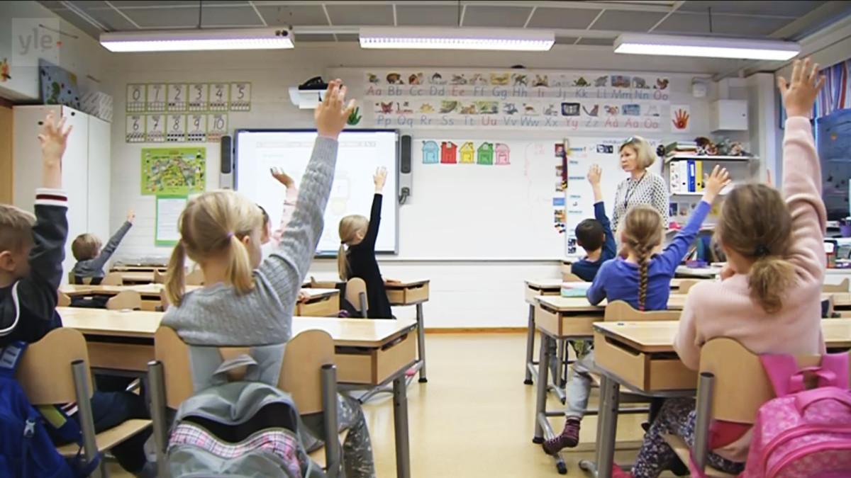 Lapsia viittaamassa luokassa.