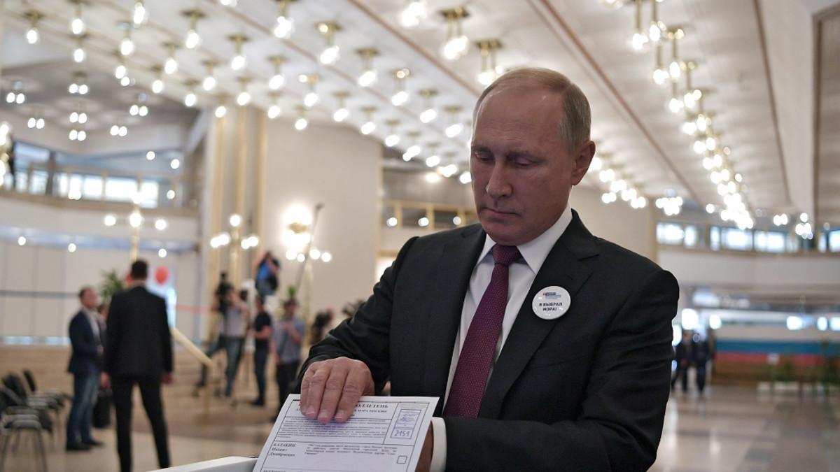 Tummaan pukuun ja viininpunaiseen kravattiin pukeutunut Putin työntää äänestyslipuketta koneeseen suuressa salissa.