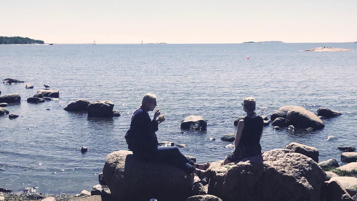 Kaksi naistaa istuu kivillä rannalla.