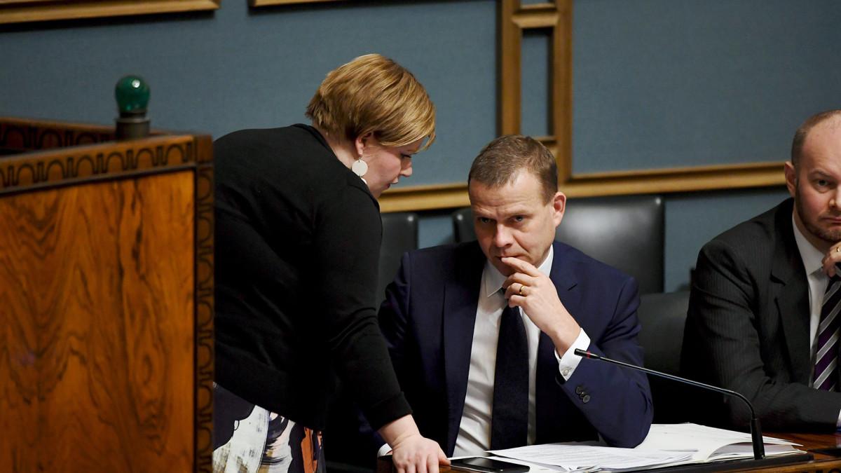Valtiovarainministeri Petteri Orpoa ja perhe- ja peruspalveluministeri Annika Saarikko keskustelevat eduskunnan täysistunnossa.
