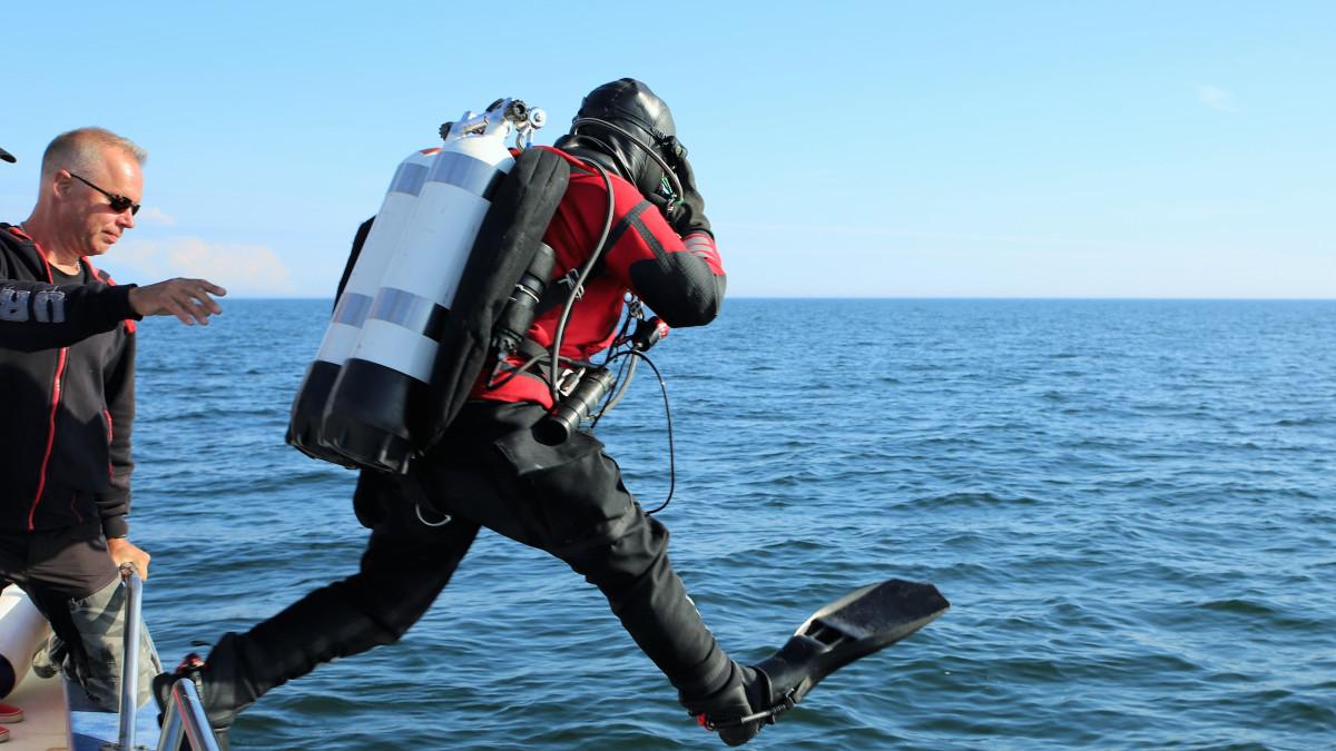 Mies hyppää veteen