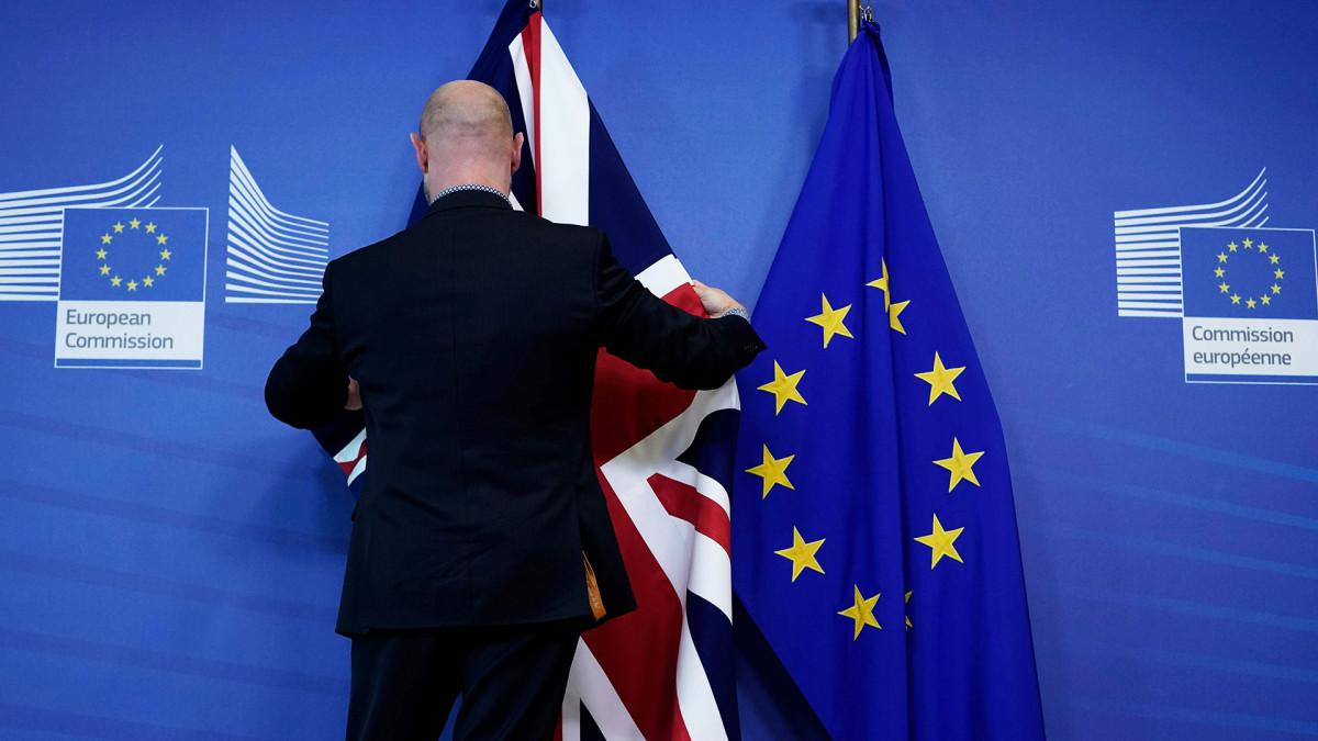 Komission työntekijä ripustaa Union Jackia EU:n tähtilipun viereen huippukokouksen valmisteluissa.