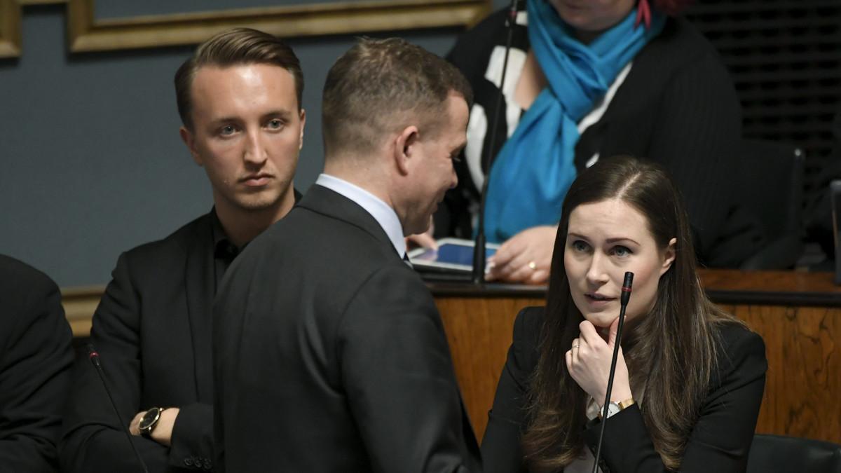 Pääministeri Sanna Marin keskustelee Kokoomuksen puheenjohtajan Petteri Orpon kanssa eduskunnan täysistunnossa 18. maaliskuuta.