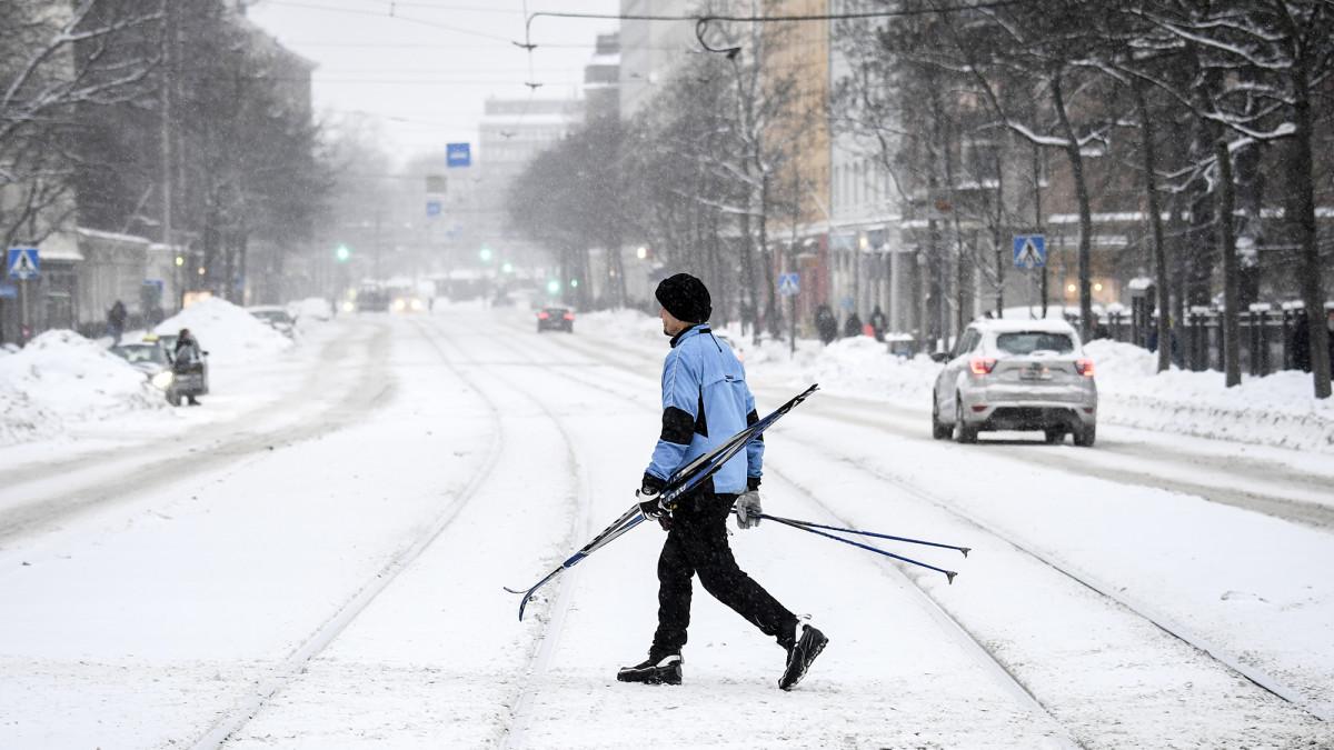 Suksia kantava mies ylittää lumipyryssä katua Helsingissä.