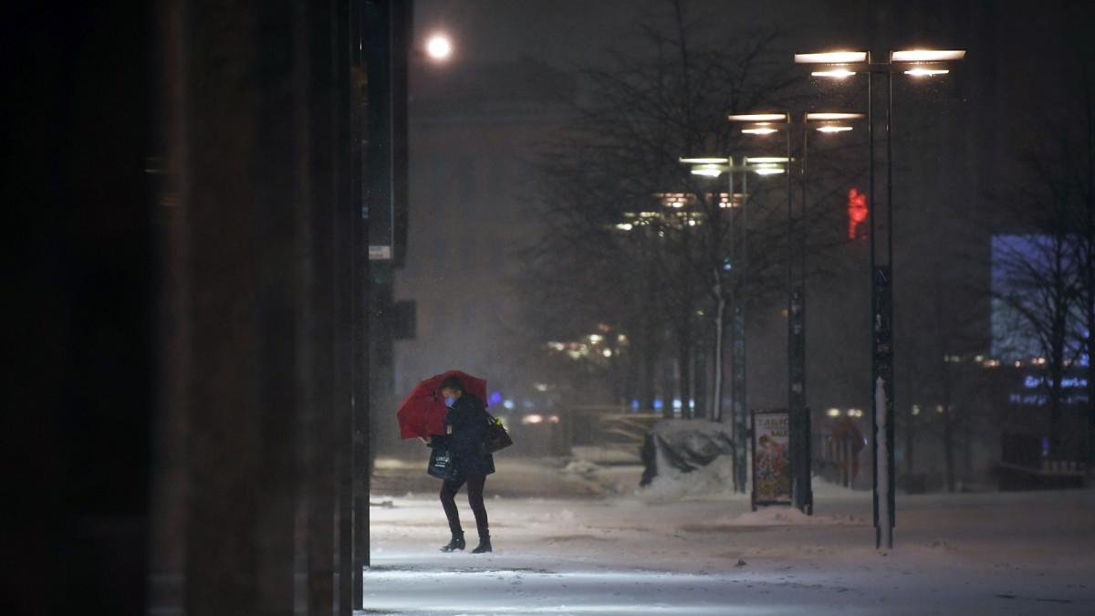 Sateenvarjolla varustautunut jalankulkija lumisateessa Helsingissä.
