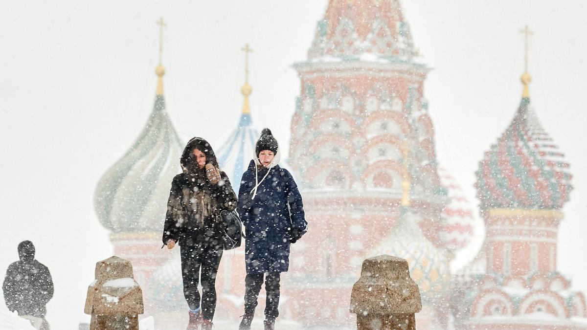 Kaksi naista kävelee lumipyryssä Moskovan Punaisella torilla.