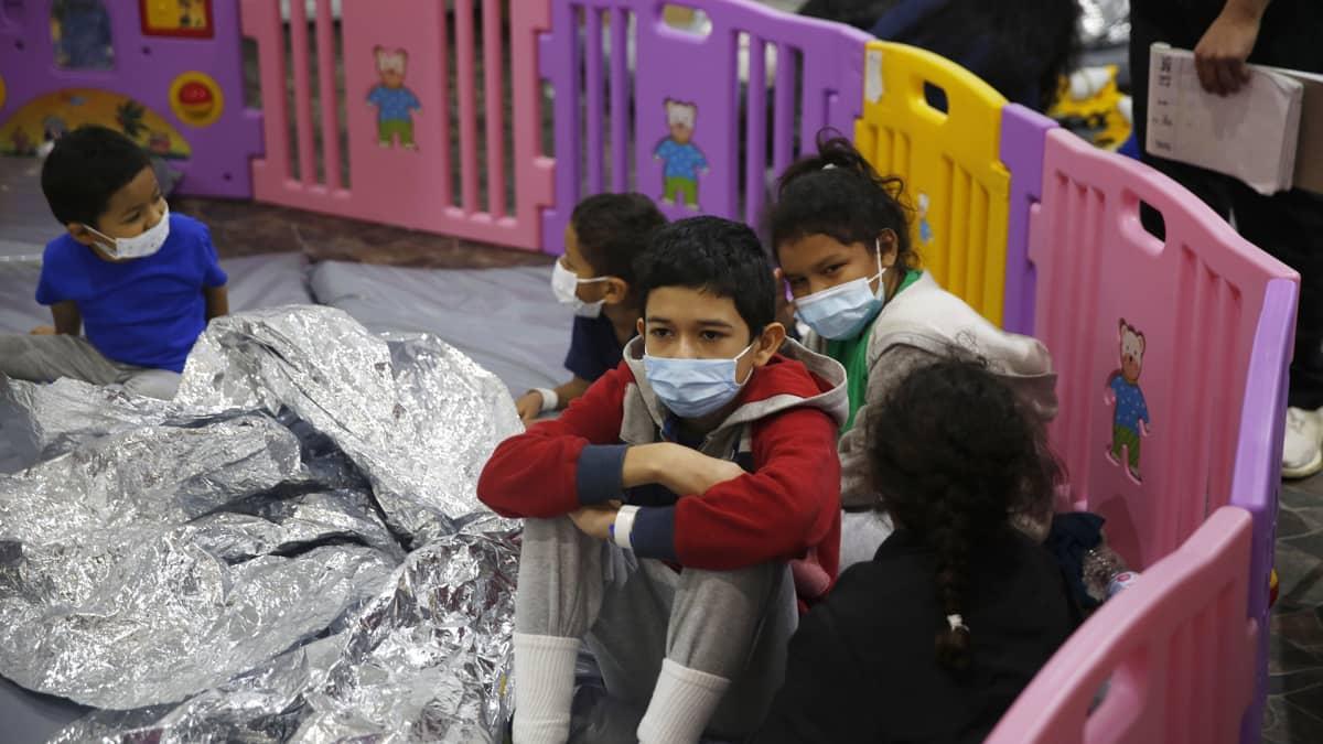 siirtolaislapsia leikkiaitauksessa pakolaiskeskuksessa maskit kasvoillaan
