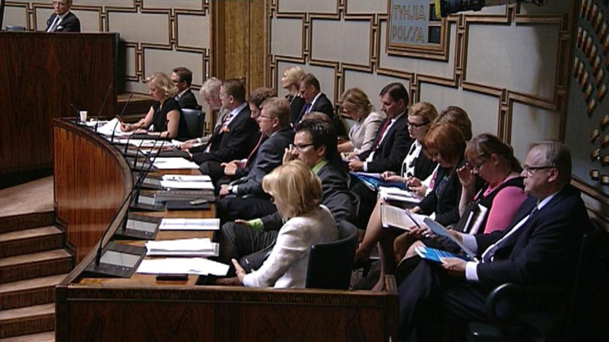Ministerit istuvat hallituksen aitiossa eduskuntasalissa.