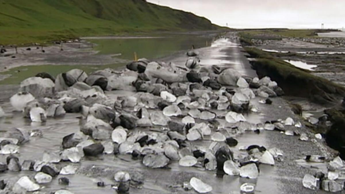Jäätiköstä irronneita jääkimpaleita ja tulvavettä maantiellä Islannissa.