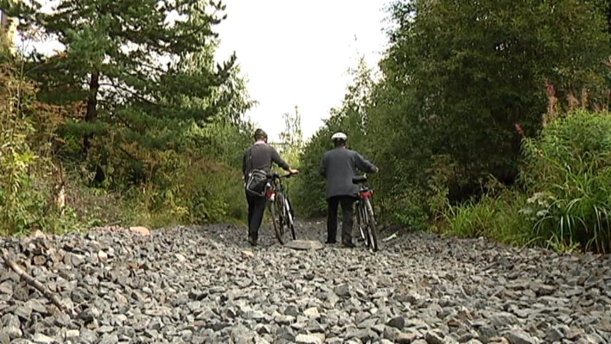 Pyöräilijät taluttavat pyöriä vanhaa ratapohjaa pitkin
