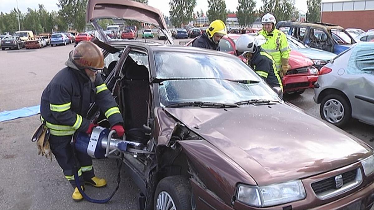 Palomies katkaisee auton A-pilaria.