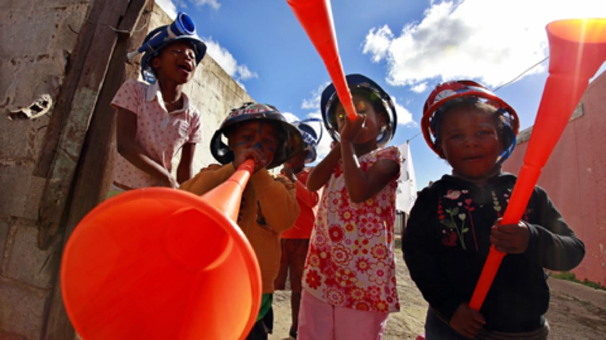 Eteläafrikkalaislapset puhaltelevat vuvuzela-torveen.