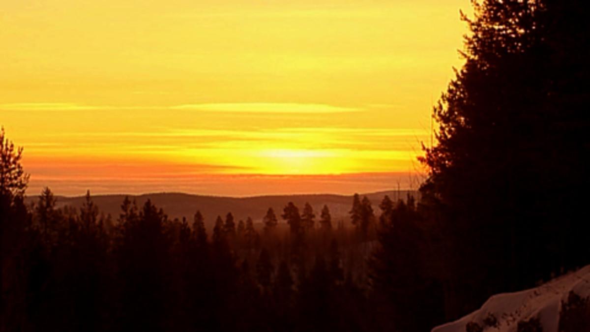 Horisontin alle painunut aurinko on värjännyt taivaan punertavaksi Inarissa