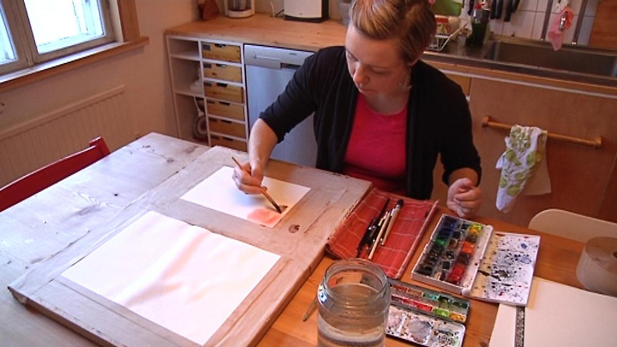 Graafikko Elina Warsta maalaa keittiön pöydän ääressä.