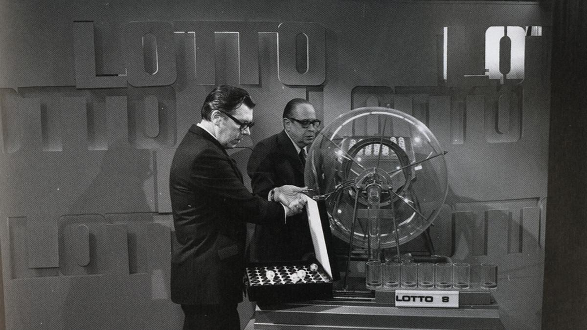 Lottokone ja viralliset valvojat vanhassa valokuvassa.