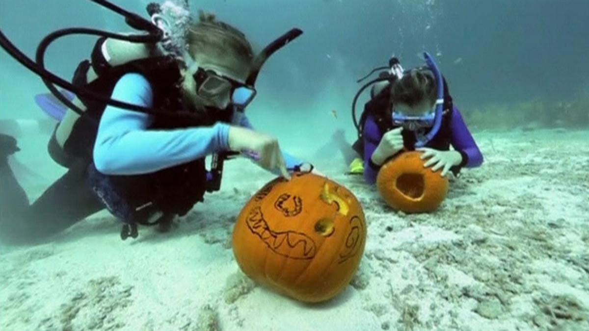Sukeltajat kaivertavat kurpitsoita veden alla.