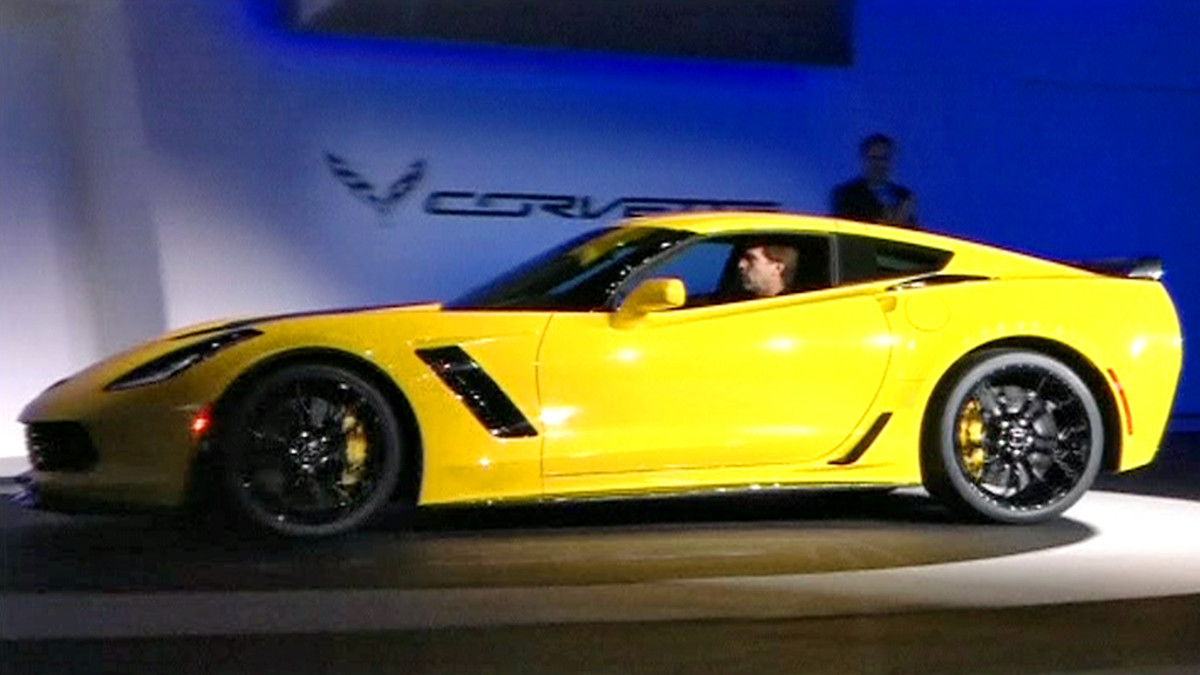 Keltainen Corvette ajaa isolle näyttämölle Detroitin autonäyttelyssä.