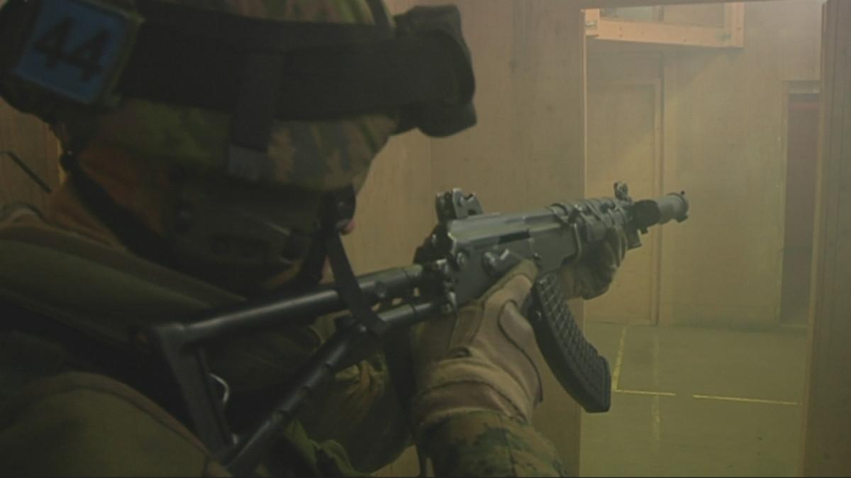 Sotilas tähtää aseella tyhjään huoneeseen.