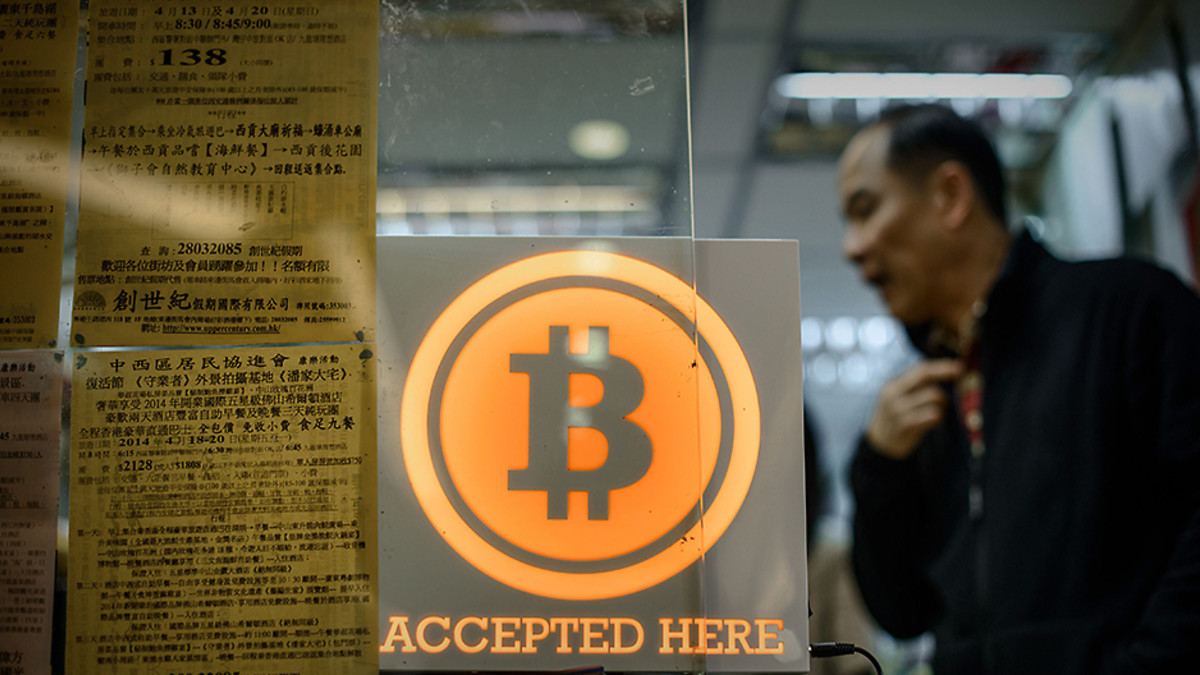 """Aasialainen mies asioi kaupassa lasin takana. Etualalla Bitcoinin symboli ja teksti """"Accepted here""""."""