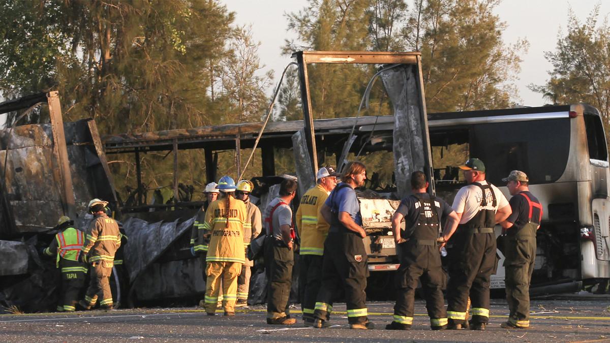 Pelastustyöntekijöitä palaneen bussin edessä.