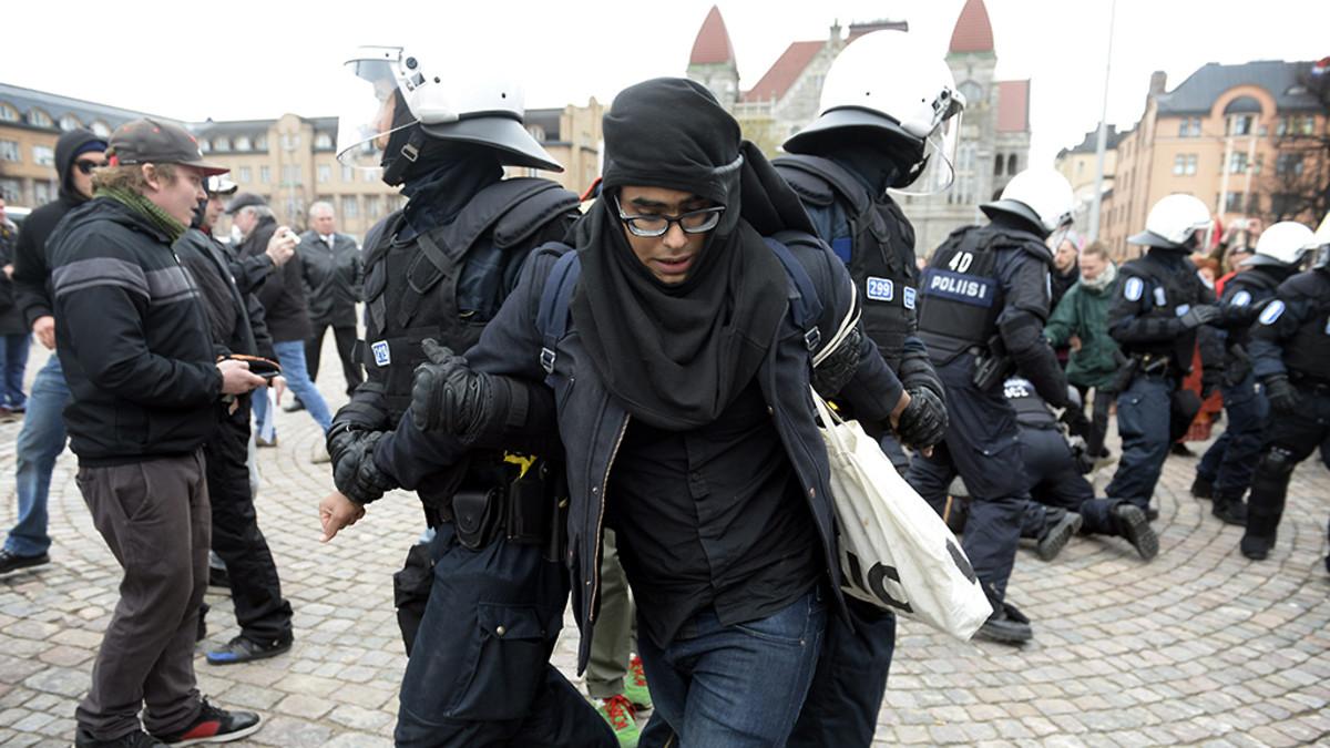 Poliisit ottavat kiinni mielenosoittajaa vappumarssilla.