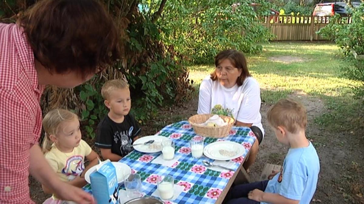 Lapsia ja ohjaajia ruokapöydän ääressä.
