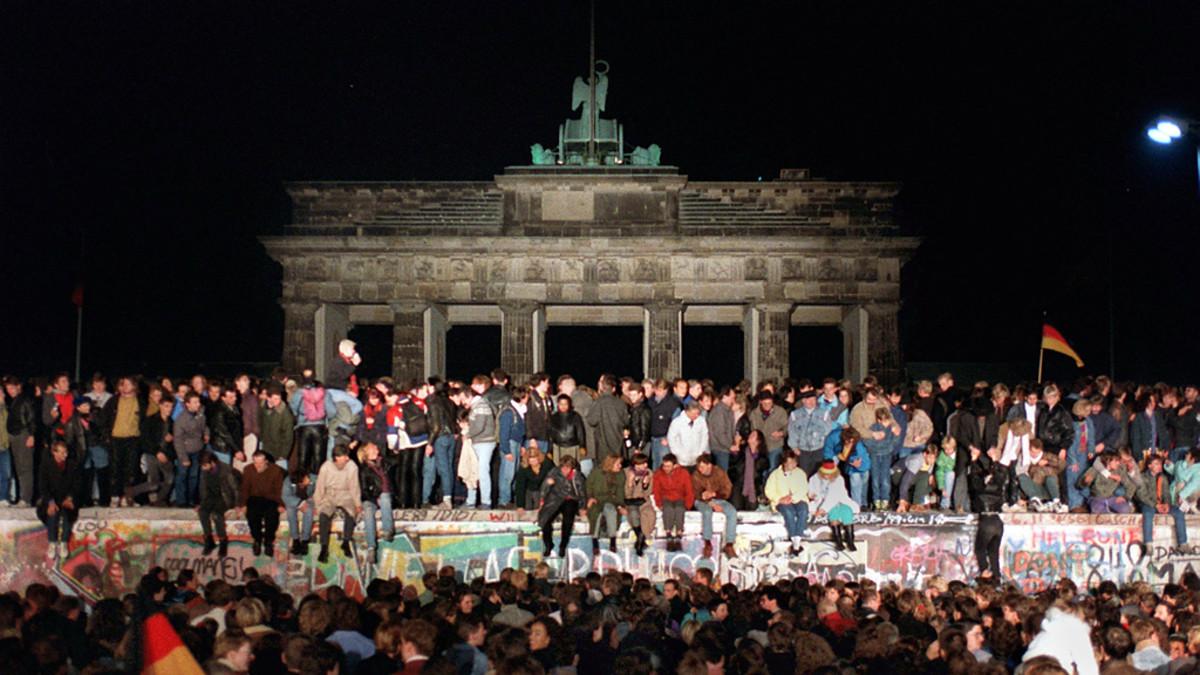 Ihmisiä Berliinin muurin päällä Brandenburgin portilla.