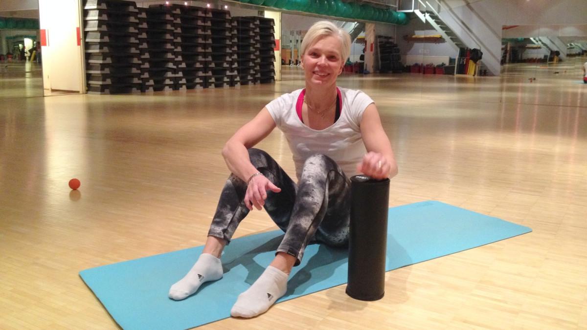 Liikunnanohjaaja Saara Kokko näyttää, miten putkirullalla hierotaan kehon lihakset.