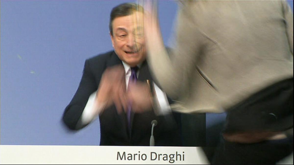 Nainen hyppää Mario Draghin pöydälle.