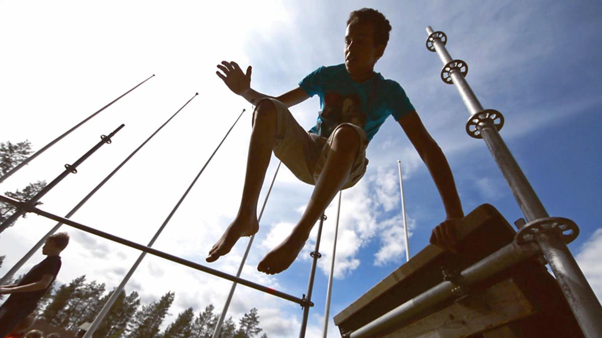 Poika hyppää esteen yli