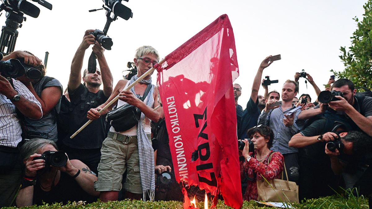 Nainen polttaa Syrizan lippua.