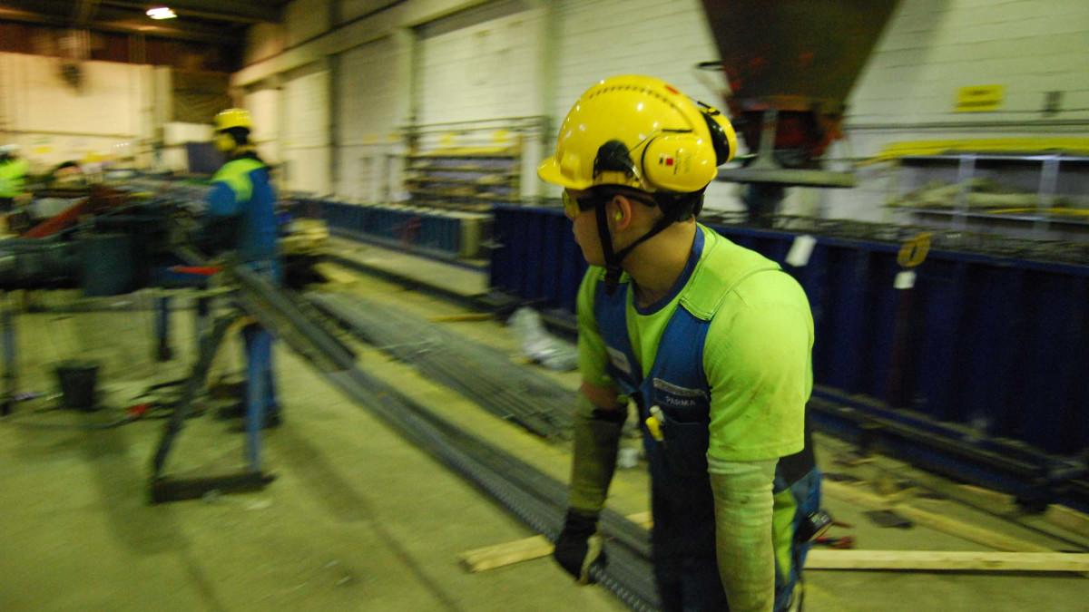 Työntekijät kantavat harjateräksiä Parman Uuraisten tehtaalla.