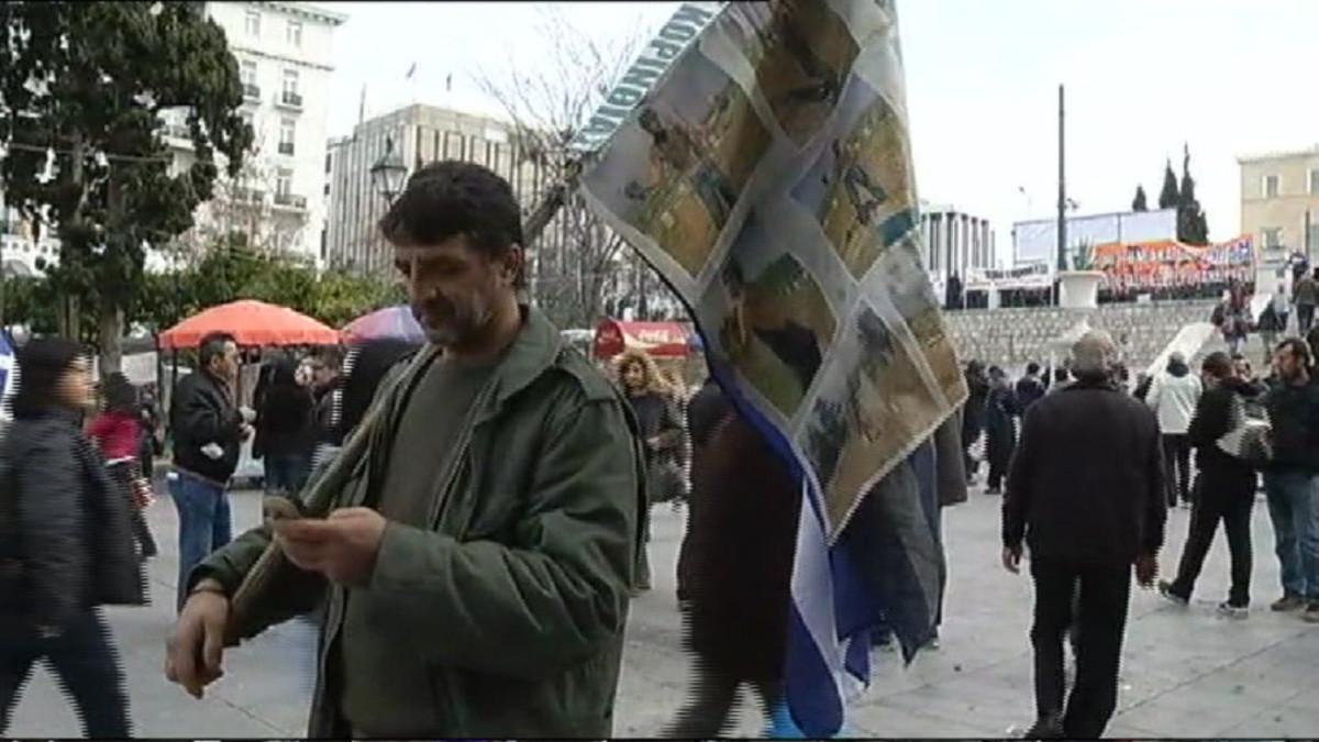 Mies katselee kännykkäänsä Ateenassa.