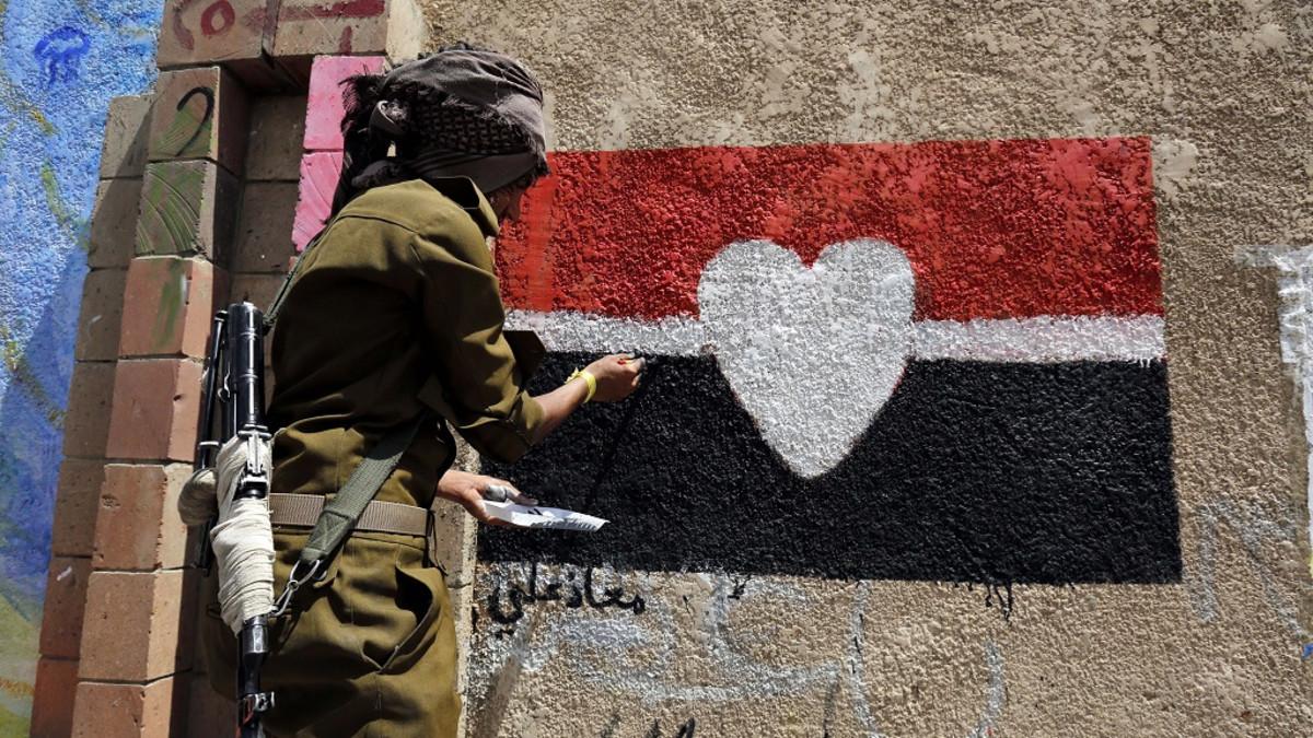 Naamioitunut ja aseistautunut sotilas maalaa muuriin Jemenin lippua, jonka keskellä on sydän.