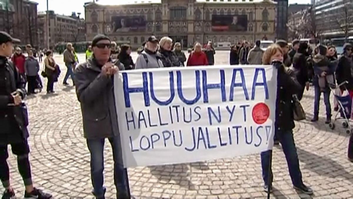 ihmisiä banderollin kanssa torilla