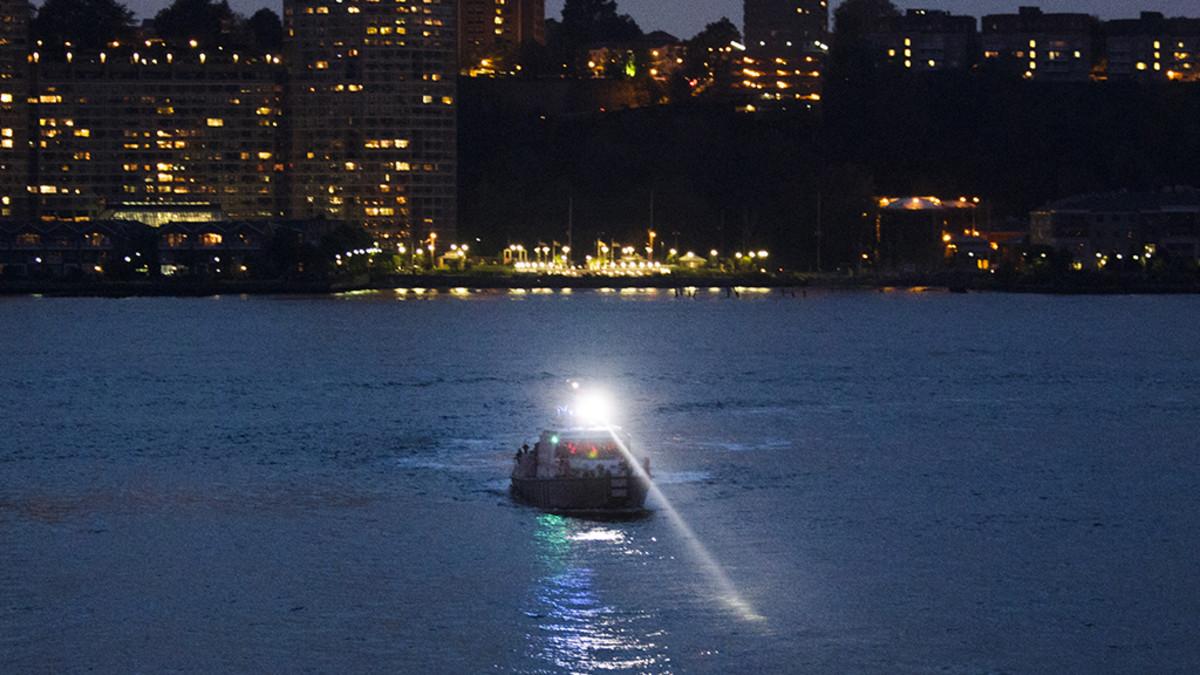 Vene ja kirkas valonheitin joella.