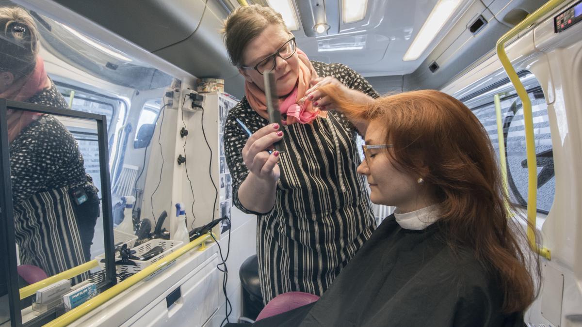 Nainen kampaa asiakkaan hiuksia parturiautossa