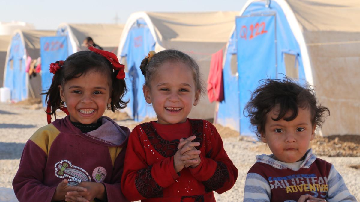 Iloisia lapsia telttaleirissä.